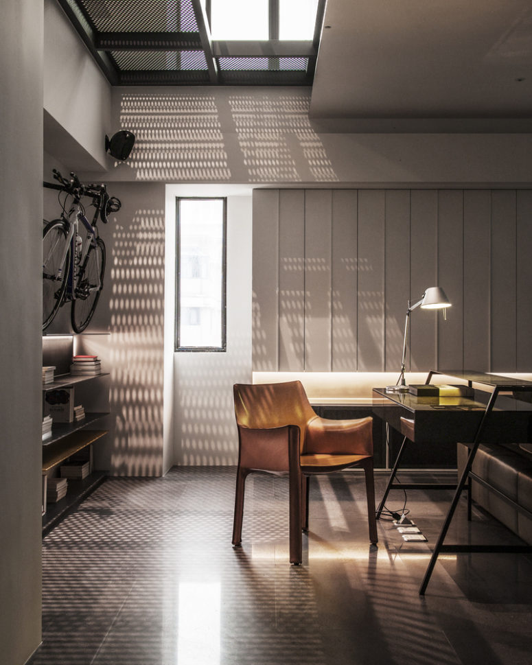 The metal mesh screen marks an opening in the ceiling and lets light run through, creating a pattern on the floor