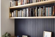 06 a black wall and light-colored wooden floating shelves plus a desk below for reading and studying