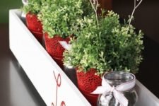 06 a stylish centerpiece in a box with red lace pots, greenery and wire hearts in the pots