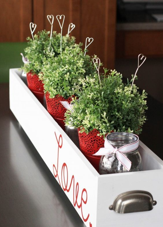 a stylish centerpiece in a box with red lace pots, greenery and wire hearts in the pots