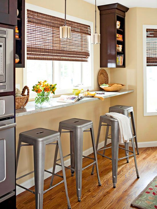 a windowsill breakfast bar with industrial stools and some storage shelves on both sides