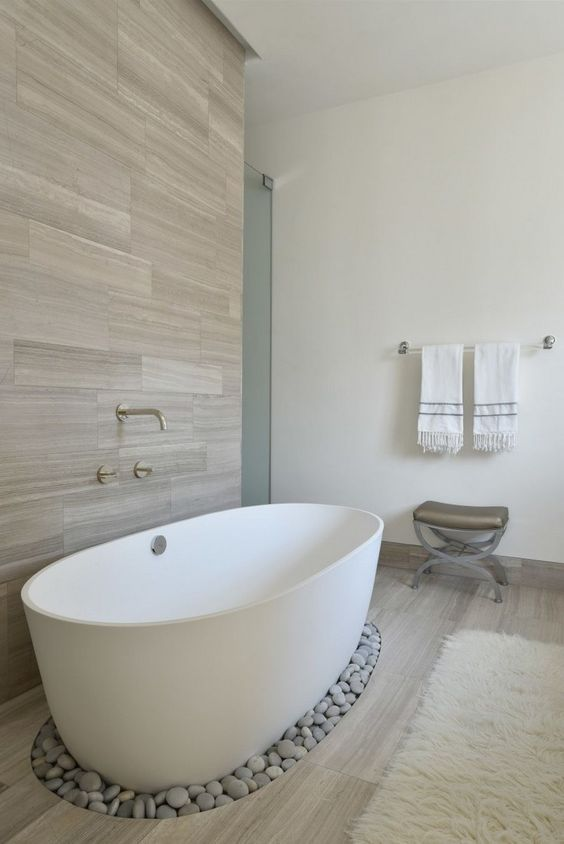 a wood clad wall and some pebbles under the bathtub add a spa feel to the space