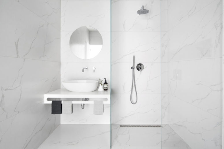 The bathroom is completely covered with white marble for a chic modern look
