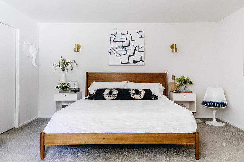 The bedroom features a wooden bed, white floating nightstands and some brass touches