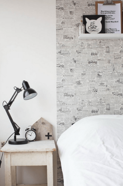 The headboard wall is enlivened with newspaper-like wallpaper