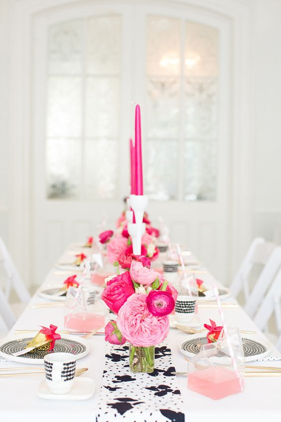 a black and white table setting with pink and hot pink florals and candles