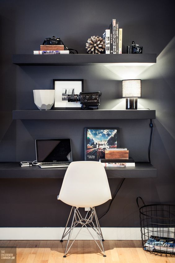 a black wall with floating shelves and a desk with displays and much light