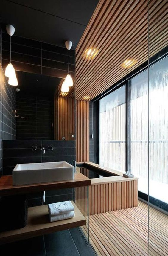 a contemporary bathroom with a spa feel, which is achieved with wood and a wood clad bathtub