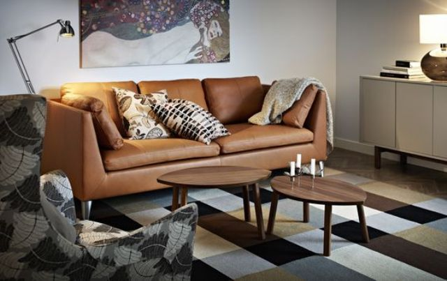 a cozy living room with a tan leather Stockholm sofa and a printed rug