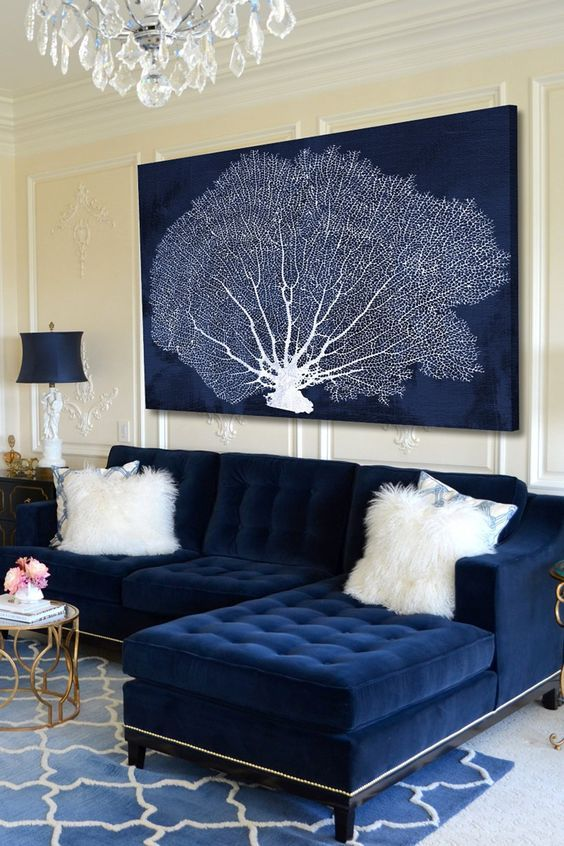 a navy artwork with a coral perfectly matches the sofa and hints on the ocean location of the home