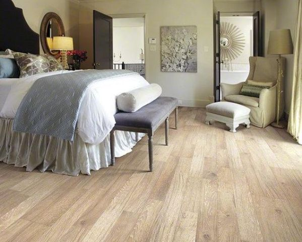 a vintage styled bedroom with an elegant feel and laminate flooring, which looks like wood