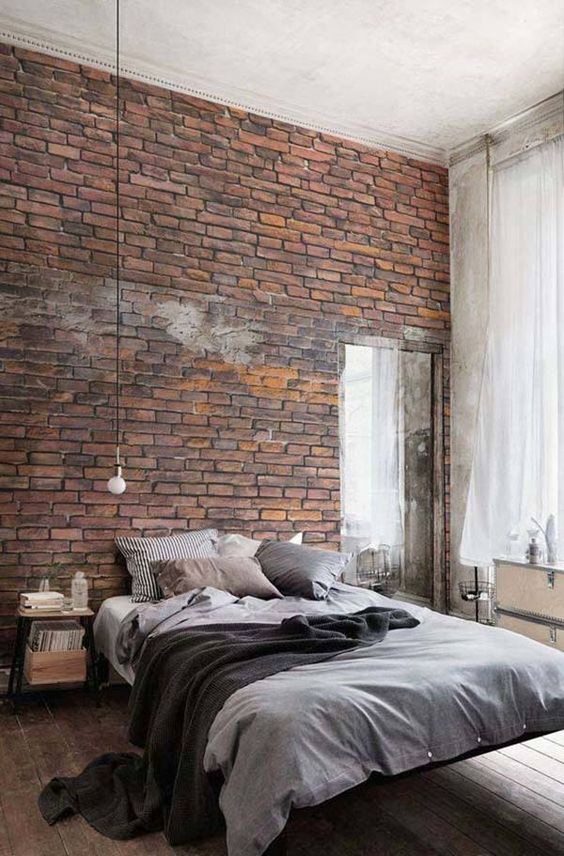 an exposed brik wall is a great idea for a masculine bedroom or an industrial space