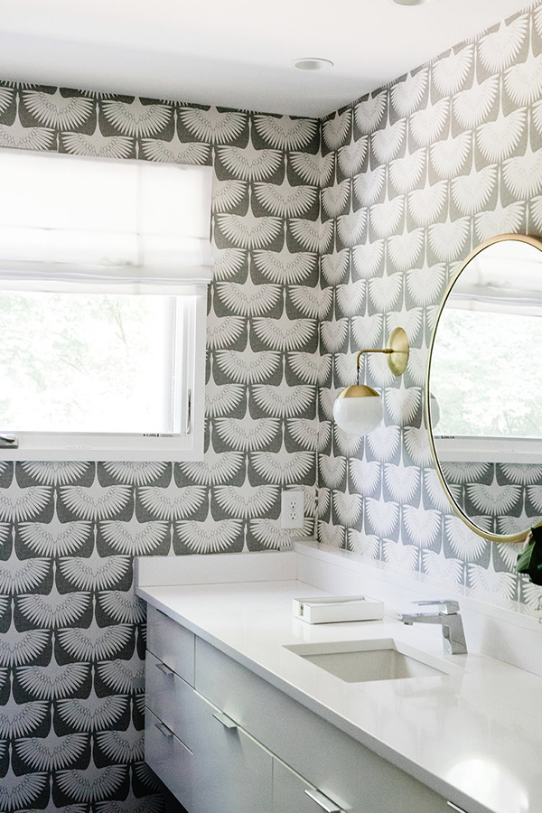 The bathroom is decorated with statement wallpaper and bold brass touches
