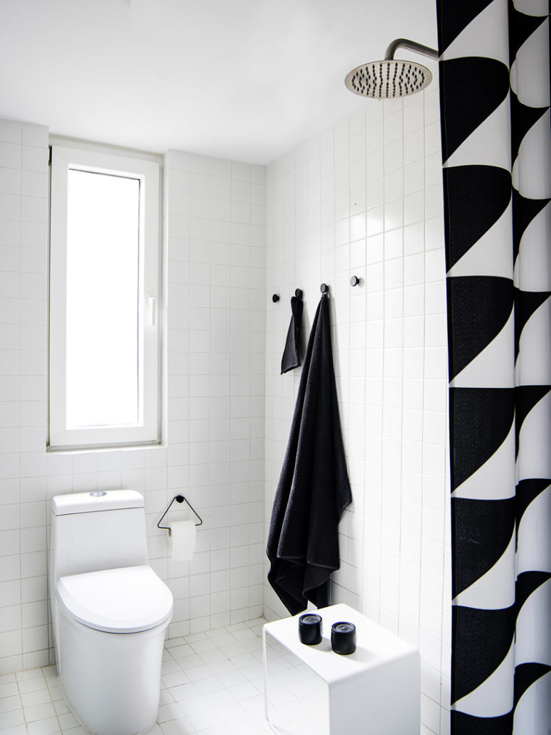 The bathroom is done in black and white, its decor is simple and laconic