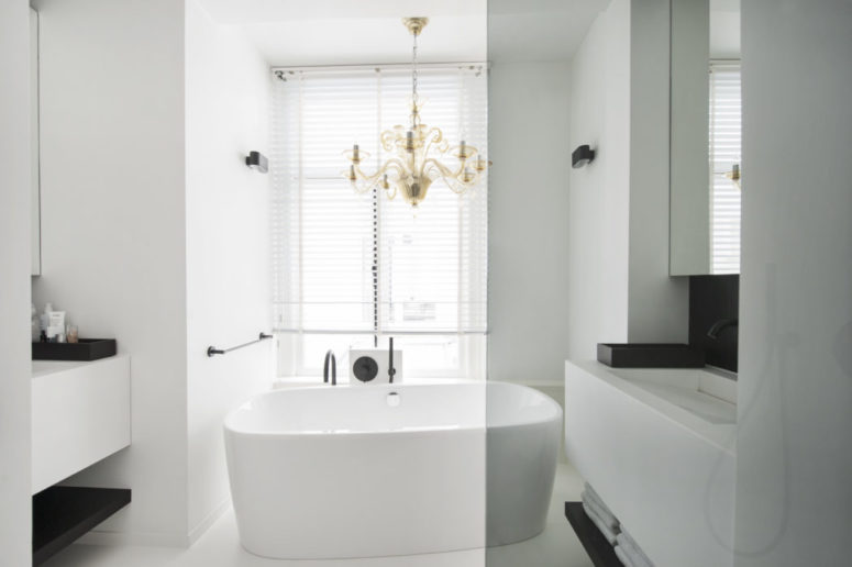 The master bathroom is done in white, with black accents and a brass chandelier over the bathtub
