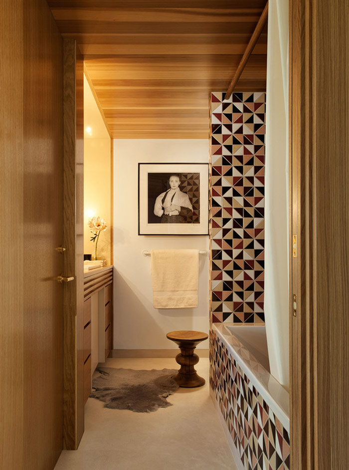The second bathroom features mosaic geometric tiles in the bathtub zone, and some wood