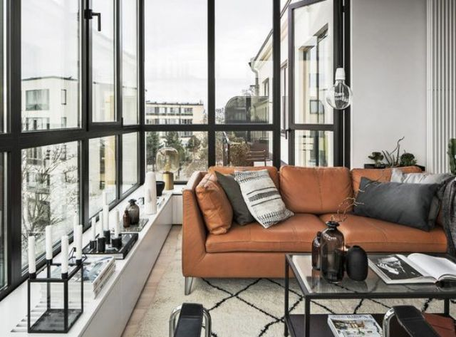 a gorgeous Scandinavian monochrome space is warmed up with a tan leather Stockholm sofa