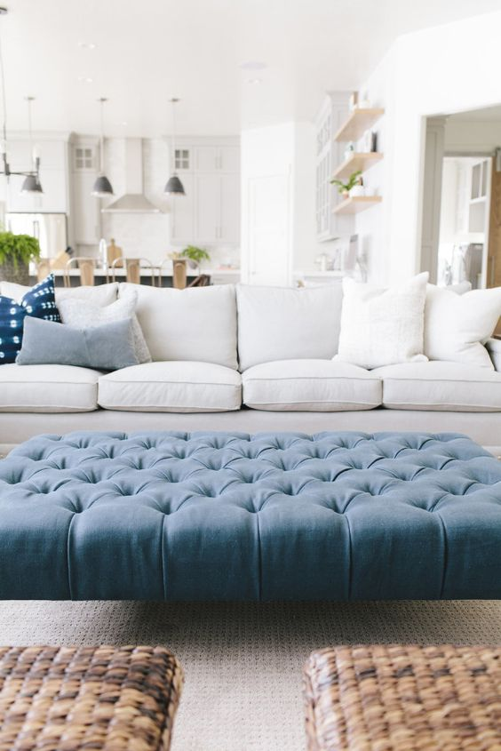 a large tufted blue ottoman hints that it's a beach space
