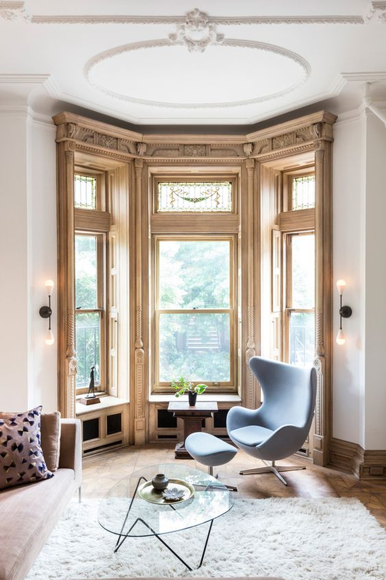 an awkward corner turned into a gorgeous reading space with large windows and an egg chair