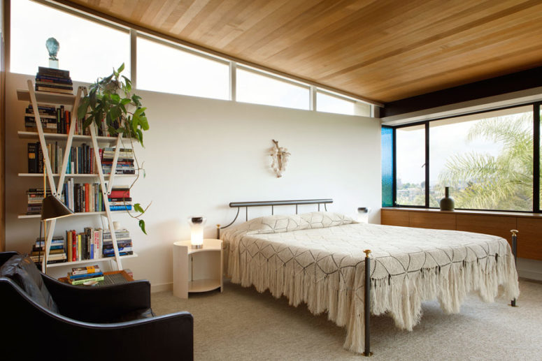 The bedroom is done with some skylights, an eye-catchy bookshelf and some more stylish mid-century furniture