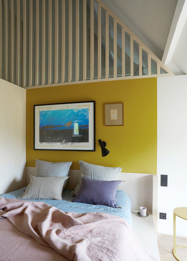 The guest bedroom is colorful, with a bold wall and bedding plus comfy furniture