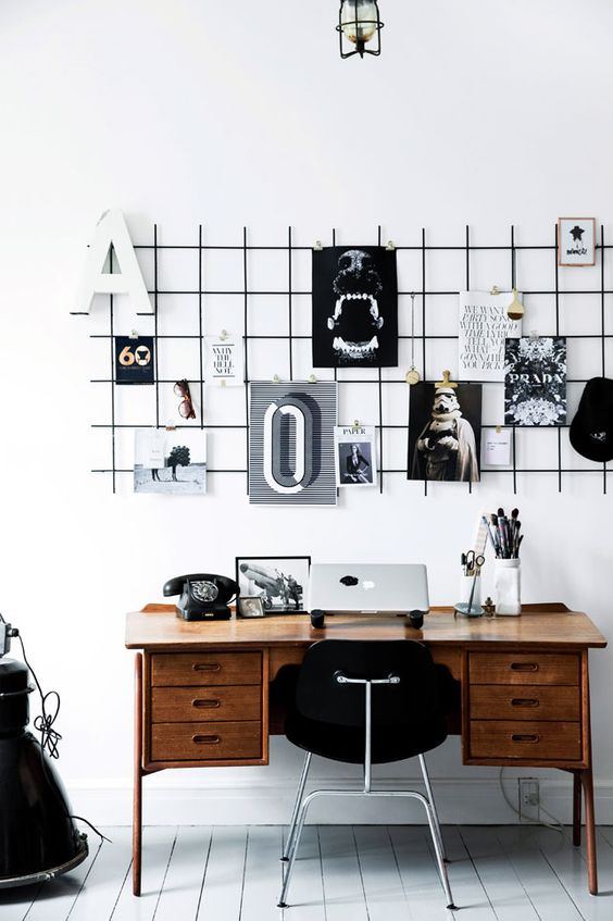 a black grid hung over the desk is a great piece to use as a pinboard
