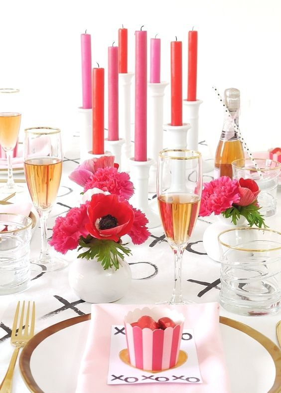 a modern tablescape with pink and red touches, blooms and candles