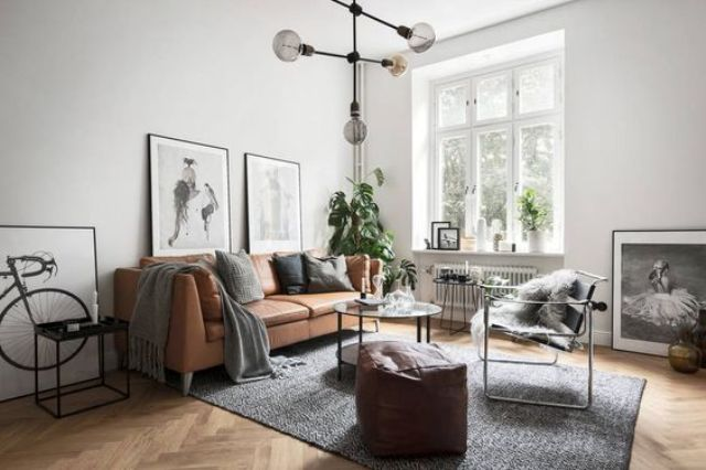 an airy and light-filled Nordic space with a tan leather sofa and ottoman looks wow