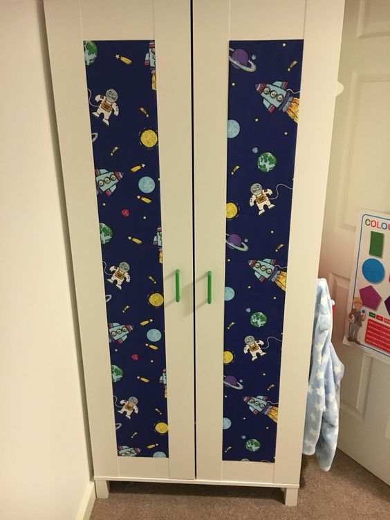 a fun Aneboda hack with bold green handles and spaceman printed wallpaper for a boy's room