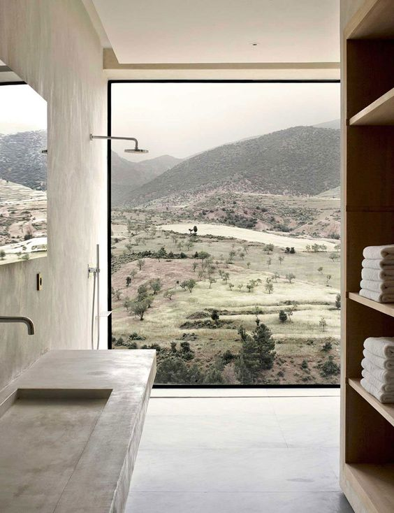 a minimalist bathroom with a glazed wall that offers stunning views of the moors