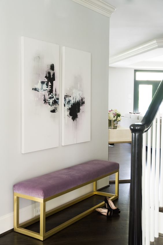 a modern glam entryway is nailed with a mauve upholstered bench and cool abstract artworks