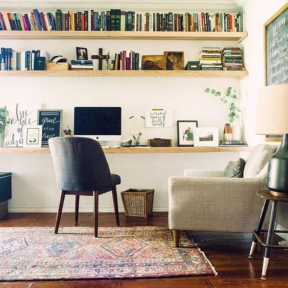 a cozy modern home office with floating shelves and a desk that go along the whole wall
