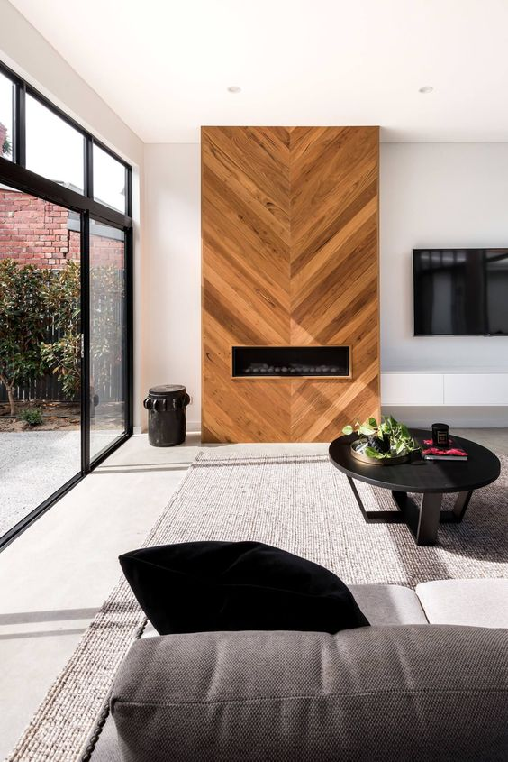 a fireplace unit clad with wood in a chevron pattern for a unique touch