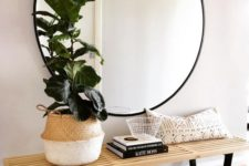 11 a mid-century modern space with a comfy bench and a large round mirror