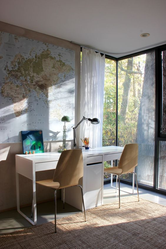 a modern double workspace or study space with Micke desks and wooden chairs next to a glazed wall