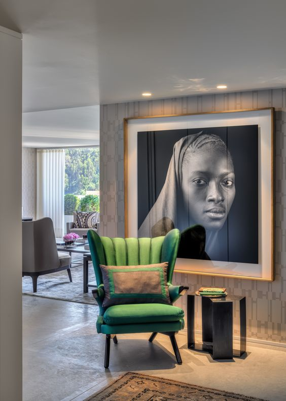 a stunning black and white photo and a bold green chair next to it make a cool accent