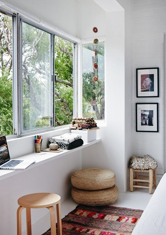 a window with a narrow windowsill used as a desk and for storage