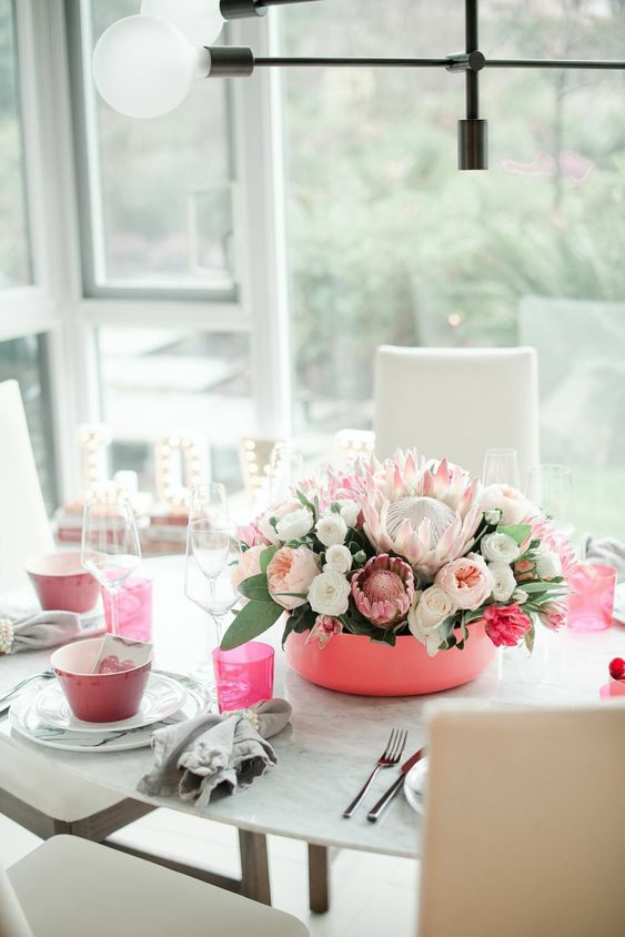 stylish Valentine's day table decor with pink bowls, glasses and a pink bowl centerpiece with lush florals
