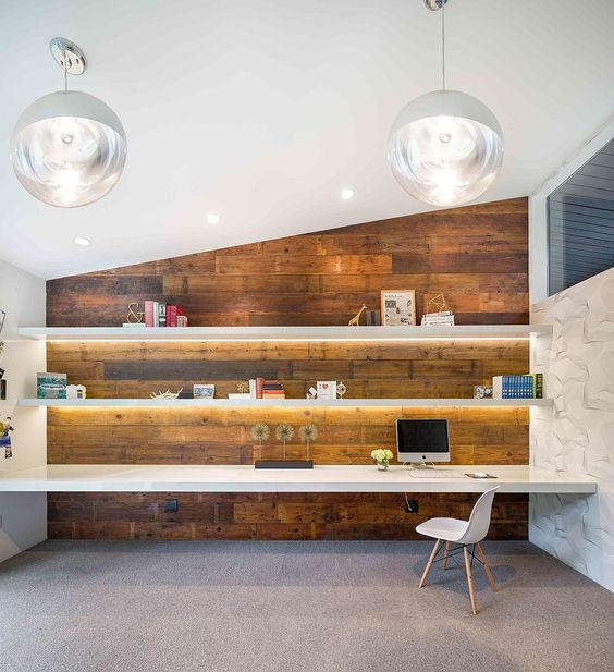a modern home office with lit up floating shelves and a matching desk in fonrt of a reclaimed wood wall