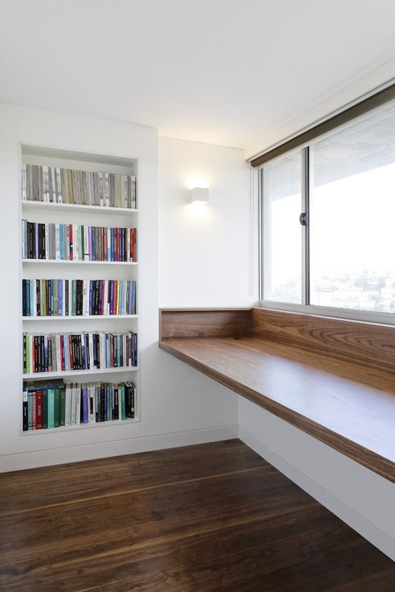 a very comfy study space with a bult-in bookcase and a large windowsill desk