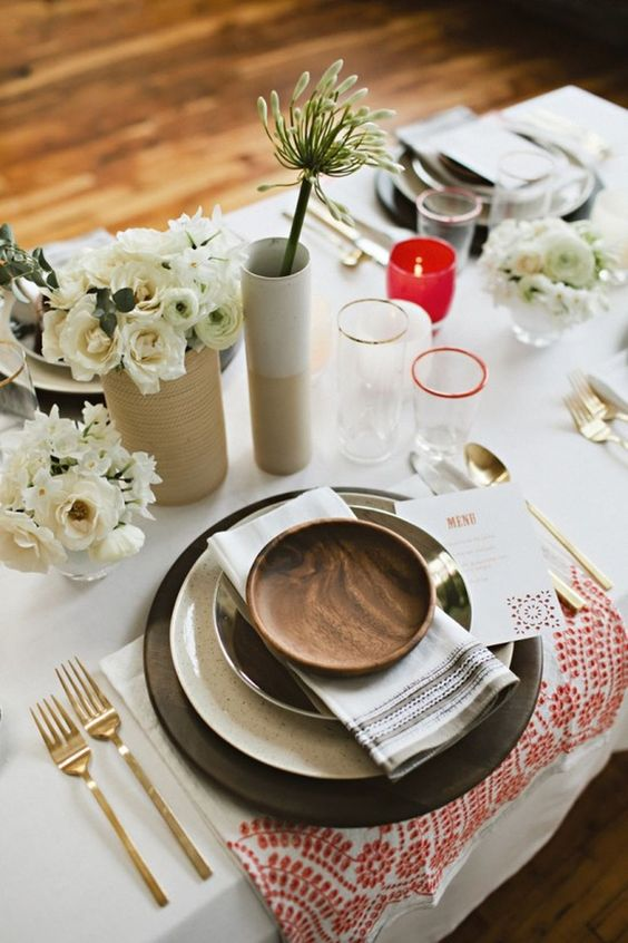 simple table decor with black chargers, neutral florals and red candle holders