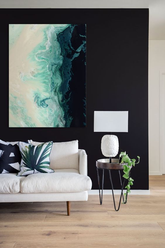 a bold statement artwork on a black wall is a chic idea and black will highlight it
