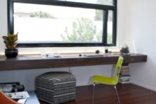 13 a modern black framed window and a thick wooden windowsill desk with a bold chair