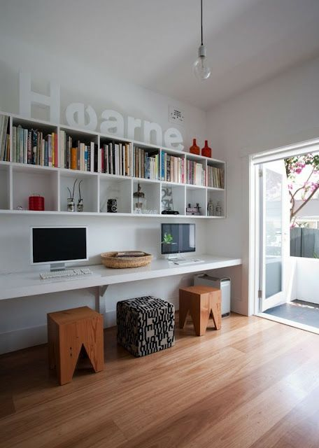 a modern shared space with floating bookshelves and a floating desk plus stools