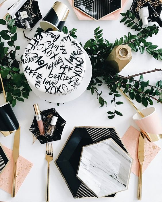 a stylish tablescape with hexagon plates and chargers, touches of marble and geometry