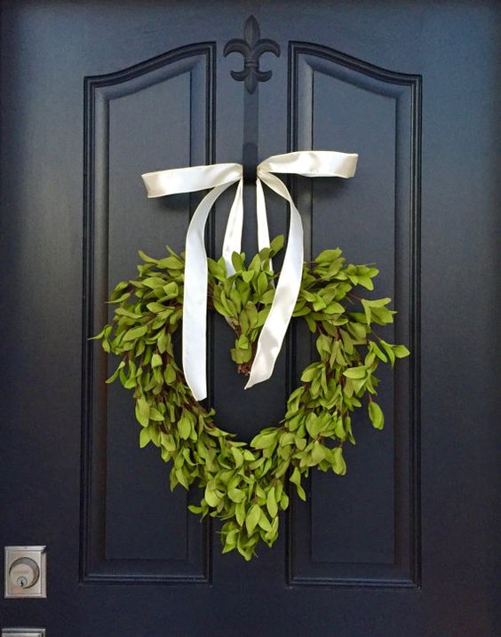 a boxwood heart wreath with a ribbon bow to decorate the front door