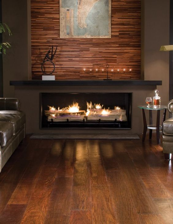 a built-in fireplace with a mantel and an accent wooden wall over it