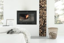 14 a minimalist white built-in fireplace with firewood storage looks very chic and bold