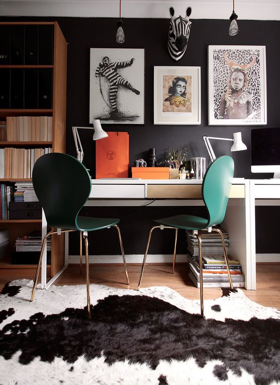 a moody workspace with a black wall, emerald chairs and a couple of Micke desks