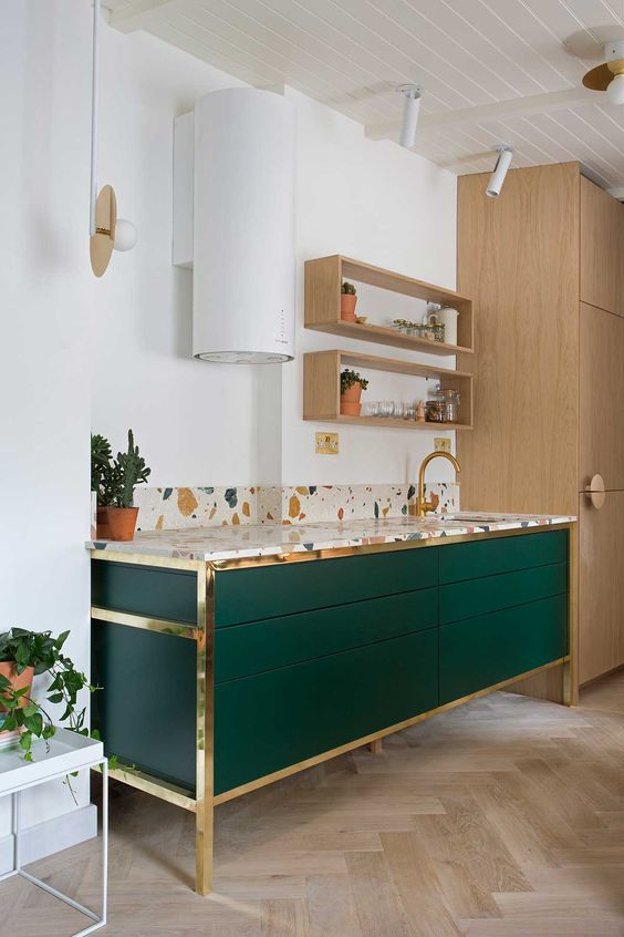 an emerald cabinets with brass framing and a terrazzo countertop for a bold and chic look